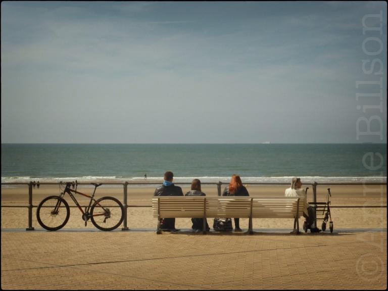 Mensen zitten of lopen naast de zee